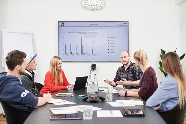 Mitarbeiter im Konferenzraum vor einem mit Diagrammen gefüllten Screen