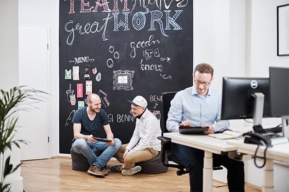 Drei Mitarbeiter am Schreibtisch und vor einer schwarzen Wand die komplett als Tafel dient