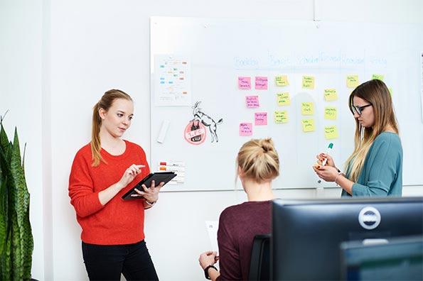 Drei Mitarbeiterinnen an einem mit Haftnotizen bestückten Whiteboard