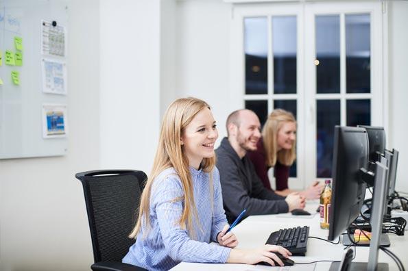 Drei Mitarbeiter an Ihren Schreibtischen
