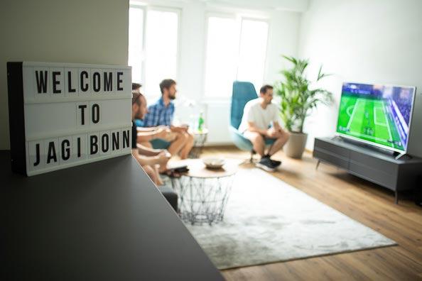 """Mitarbeiter in der Teamlounge beim Fußballschauen. Im Vordergrund eine Tafel auf der """"Welcome to JAGI-Bonn"""" steht"""