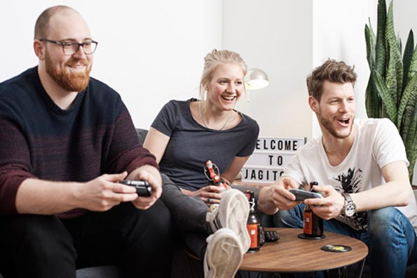 Drei Mitarbeiter spielen in der Teamlounge auf der Spielkonsole