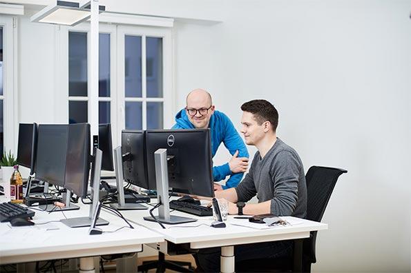Zwei Mitarbeiter besprechen sich am Schreibtisch