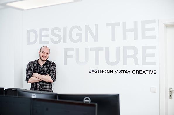 """Mitarbeiter vor einer Wand auf der in großen Buschstaben """"Design the Future"""" steht"""
