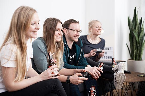 Vier mitarbeiter sitzen auf dem Sofa in der Teamlounge