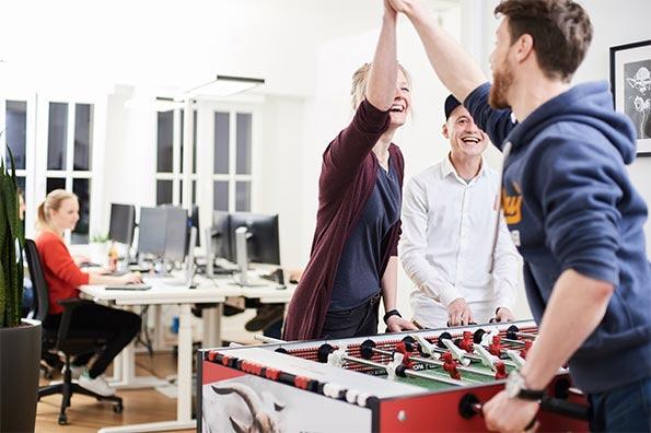 Drei Mitarbeiter Klatschen sich am Kicker gegenseitig ab